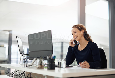 Buy stock photo Shot of a young businesswoman talking on a cellphone while working on a computer in an office