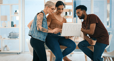 Buy stock photo Shot of a group of young designers working on a laptop together in an office