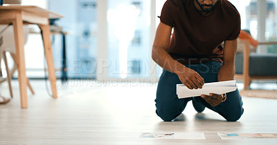 Buy stock photo Closeup shot of an unrecognisable designer spreading paperwork on a floor in an office