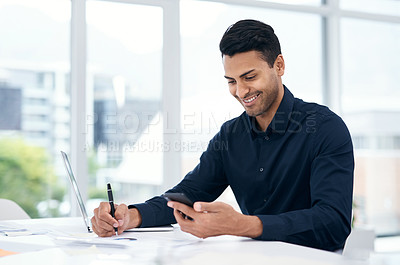 Buy stock photo Shot of a young businessman using a smartphone and laptop in a modern office