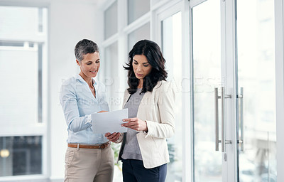 Buy stock photo Shot of two businesswomen going over paperwork in a modern office