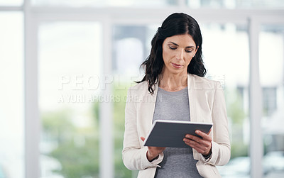 Buy stock photo Shot of a businesswoman using a digital tablet in a modern office