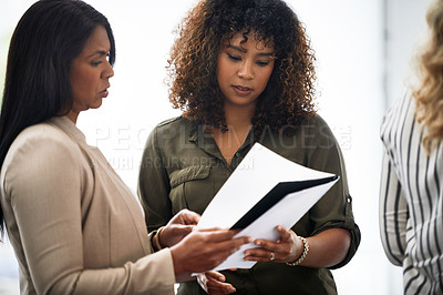 Buy stock photo Shot of two businesswoman discussing a report in a modern office