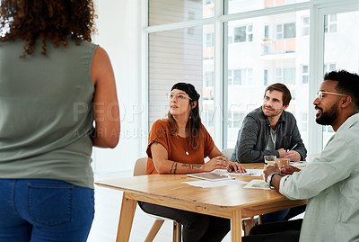 Buy stock photo Shot of a team of young businesspeople sitting in on a presentation in a modern office