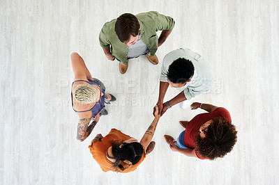 Buy stock photo High angle shot of a young businesswoman and businessman shaking hands during a team meeting in a modern office