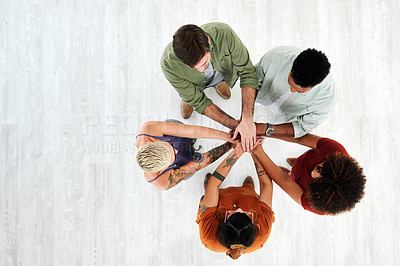 Buy stock photo High angle shot of a group of young businesspeople joining their hands in solidarity in a modern office