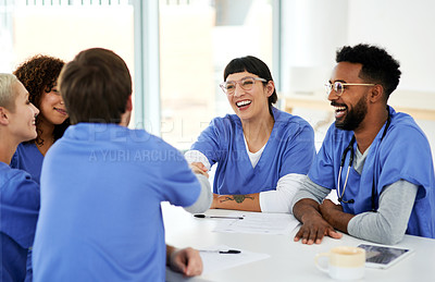 Buy stock photo Shot of a young doctor shaking hands with her colleague during a meeting in a hospital