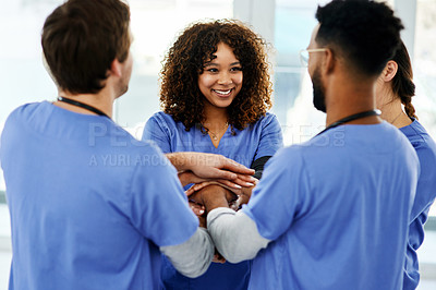 Buy stock photo Shot of a group of young doctors joining hands in solidarity in a modern hospital