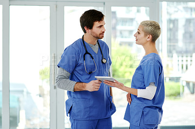 Buy stock photo Shot of two young doctors using a digital tablet together while working in a hospital