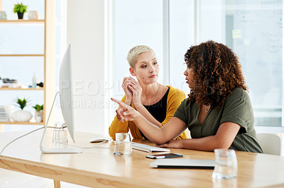 Buy stock photo Cropped shot of two businesswomen discussing something on a computer