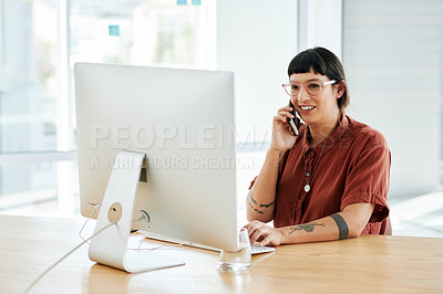 Buy stock photo Shot of a businesswoman talking on her cellphone while sitting at her desk