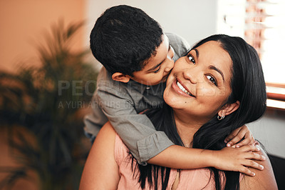 Buy stock photo Shot of an adorable little boy giving his mother a kiss on the cheek at home