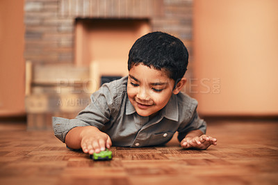 Buy stock photo Shot of an adorable little boy playing with a toy car at home
