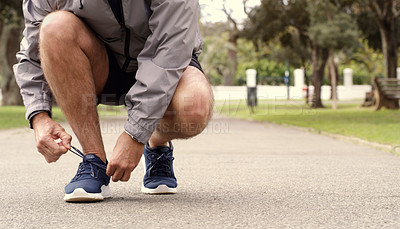 Buy stock photo Cropped shot of a senior man tying his shoelaces while out for a run in the park