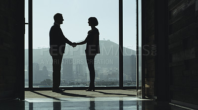 Buy stock photo Shot of two businesspeople shaking hands while standing at a window in an office