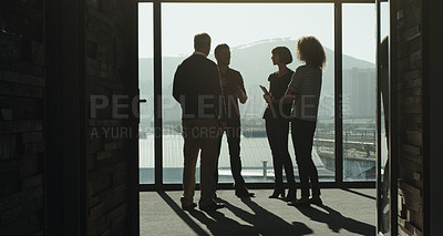 Buy stock photo Shot of a group of businesspeople having a discussion while standing at a window in an office