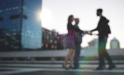 Buy stock photo Shot of a group of businesspeople shaking hands against an urban background