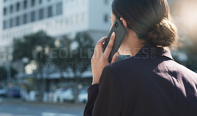 Buy stock photo Shot of a young businesswoman using a smartphone while walking through the city