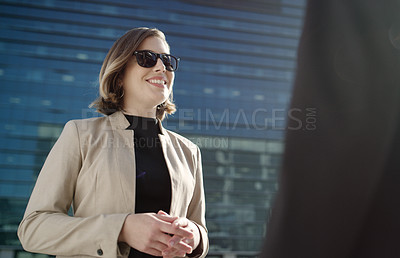 Buy stock photo Shot of a businesswoman having a discussion with a colleague against a city background