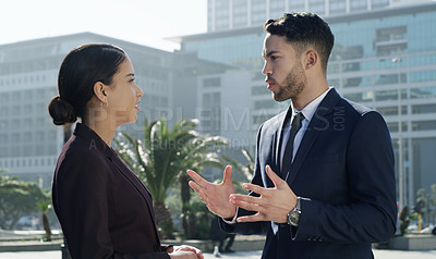 Buy stock photo Shot of a young businesswoman and businessman having a discussion against a city background