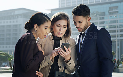 Buy stock photo Shot  of a group of businesspeople using a smartphone together against an urban background