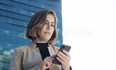Buy stock photo Shot of a young businesswoman using a smartphone against an urban background