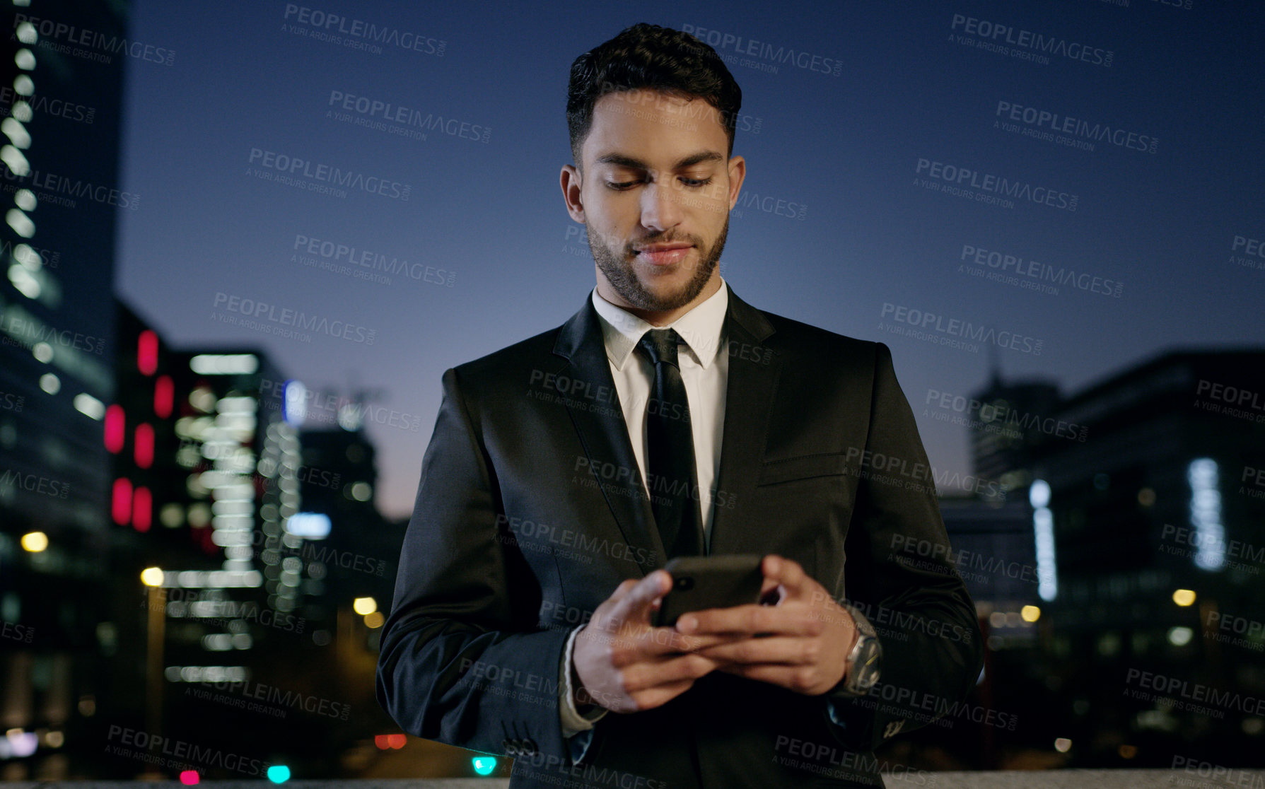 Buy stock photo Shot of a young businessman using a smartphone in the city at night