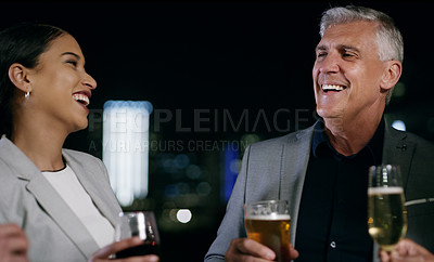 Buy stock photo Shot of a businessman and businesswoman having drinks after work in the city at night