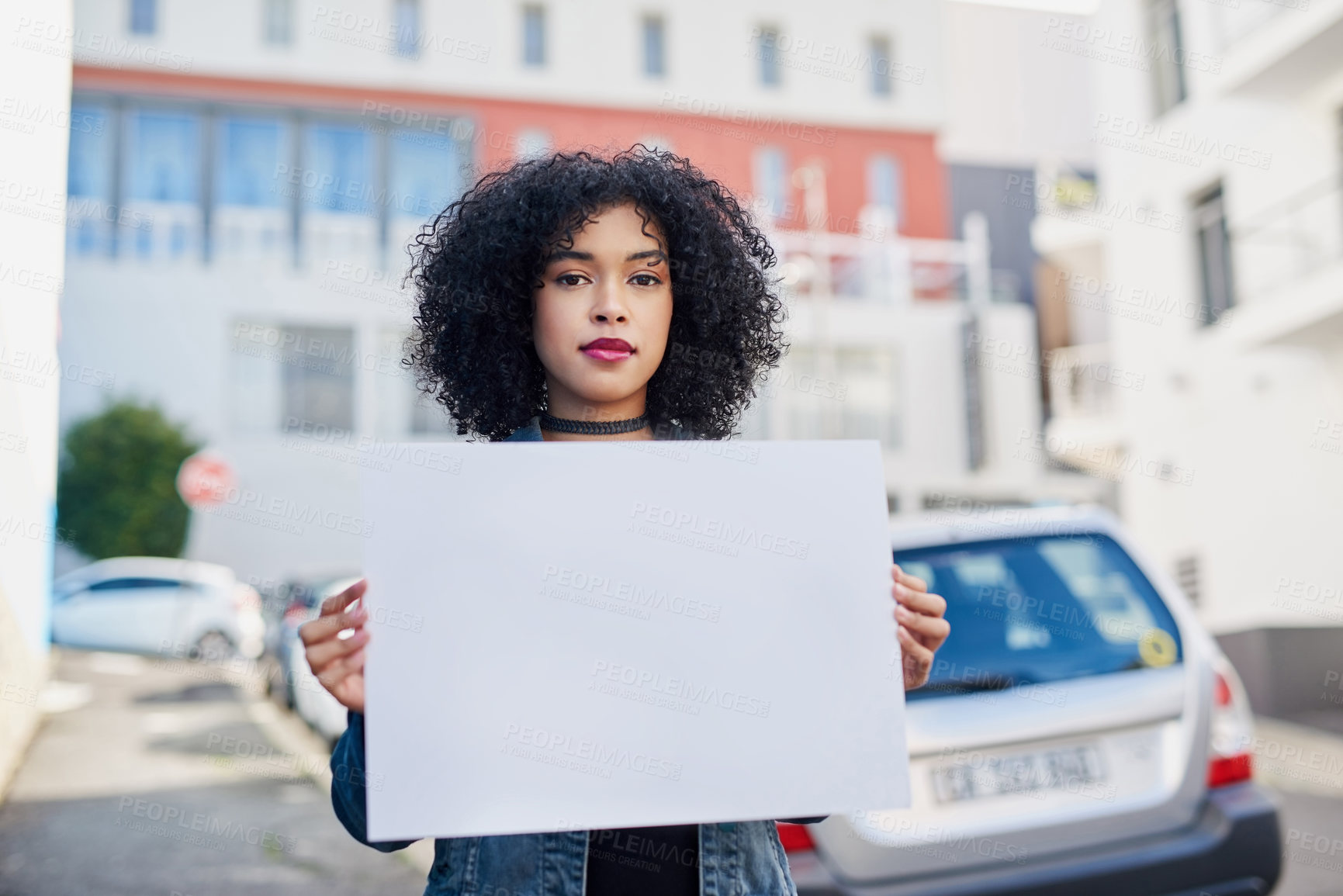 Buy stock photo Portrait of an attractive young woman holding a placard promoting equal pay between men and women in the city