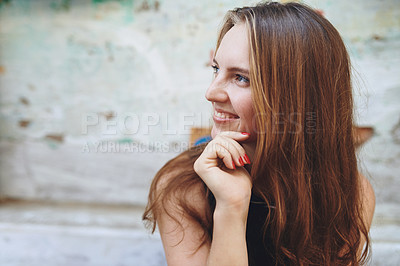 Buy stock photo Cropped shot of a young woman sitting outside while exploring a foreign city