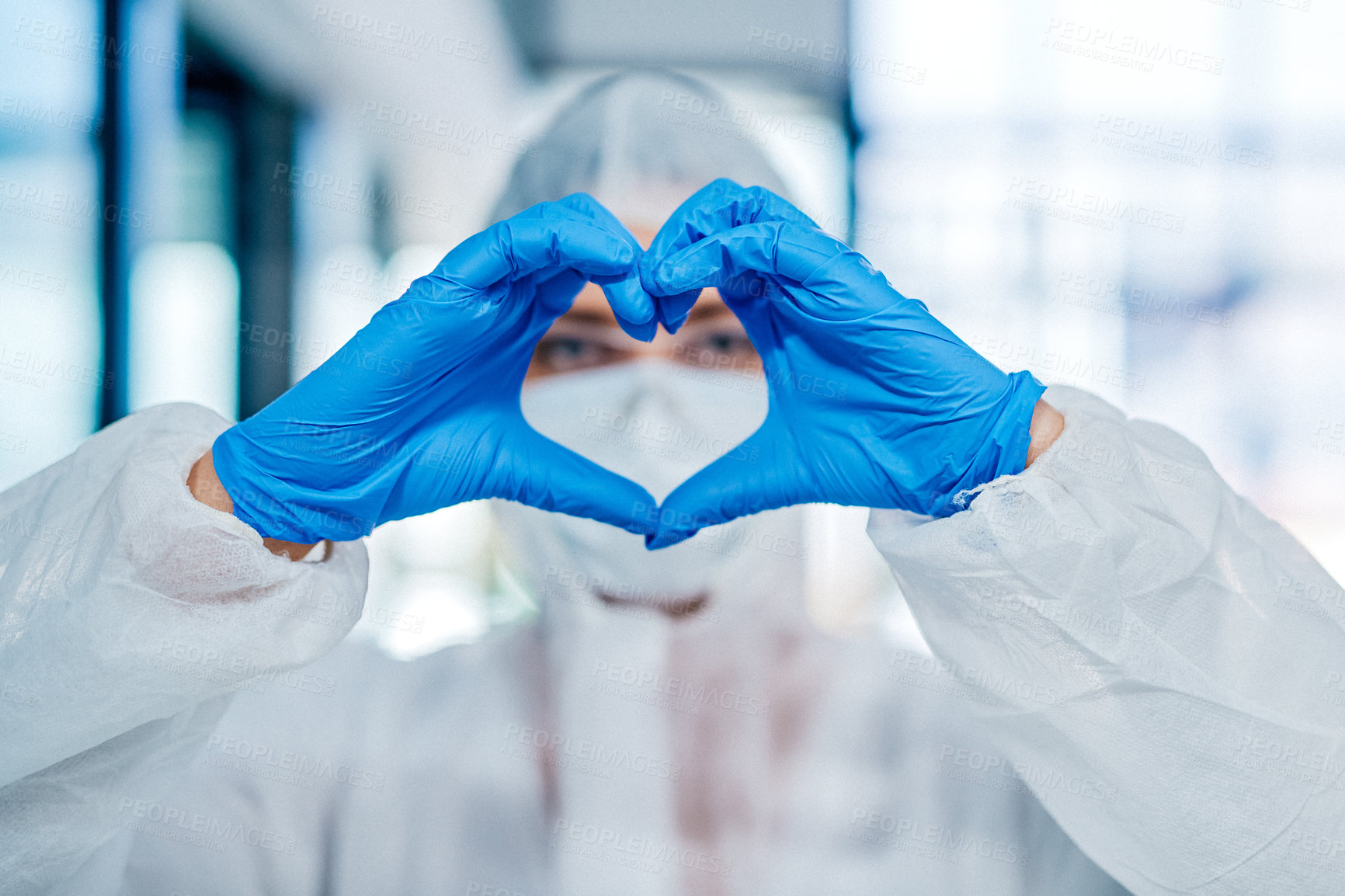 Buy stock photo Closeup shot of a healthcare worker wearing a hazmat suit and making a heart shape with her hands