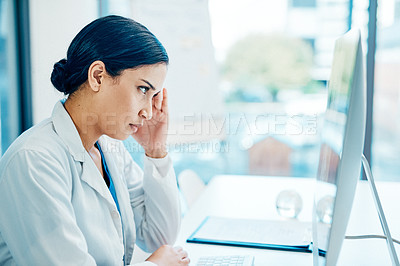 Buy stock photo Shot of a young doctor looking stressed out while working on a computer