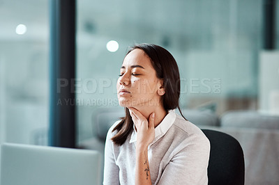 Buy stock photo Shot of a young businesswoman experiencing a sore throat while working in an office