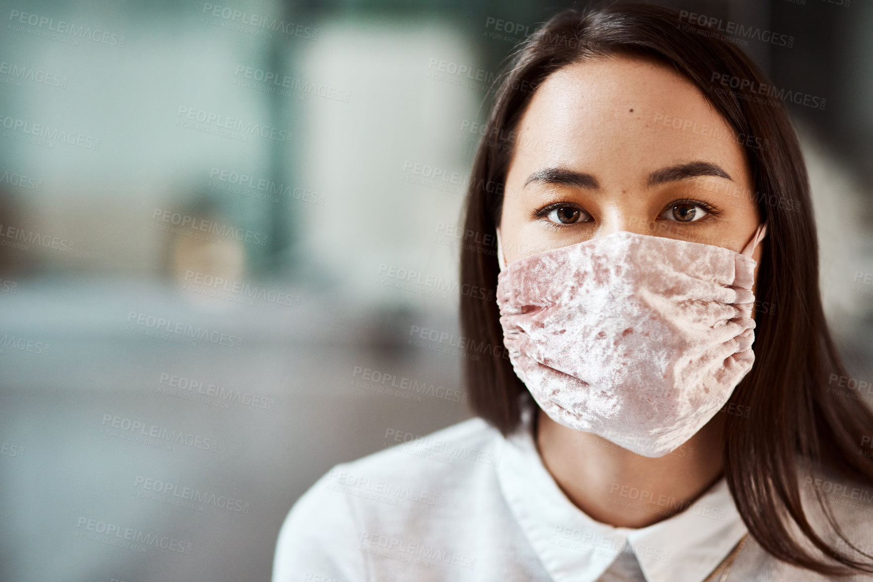 Buy stock photo Portrait of a young businesswoman wearing a mask in an office