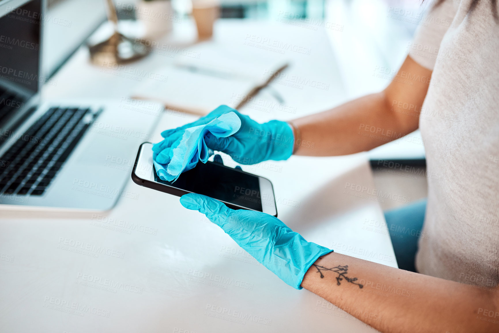 Buy stock photo Closeup shot of an unrecognisable businesswoman cleaning a cellphone in an office