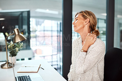 Buy stock photo Shot of a mature businesswoman experiencing neck pain while working in an office