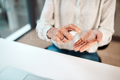 Buy stock photo Closeup shot of an unrecognisable businesswoman using hand sanitiser in an office