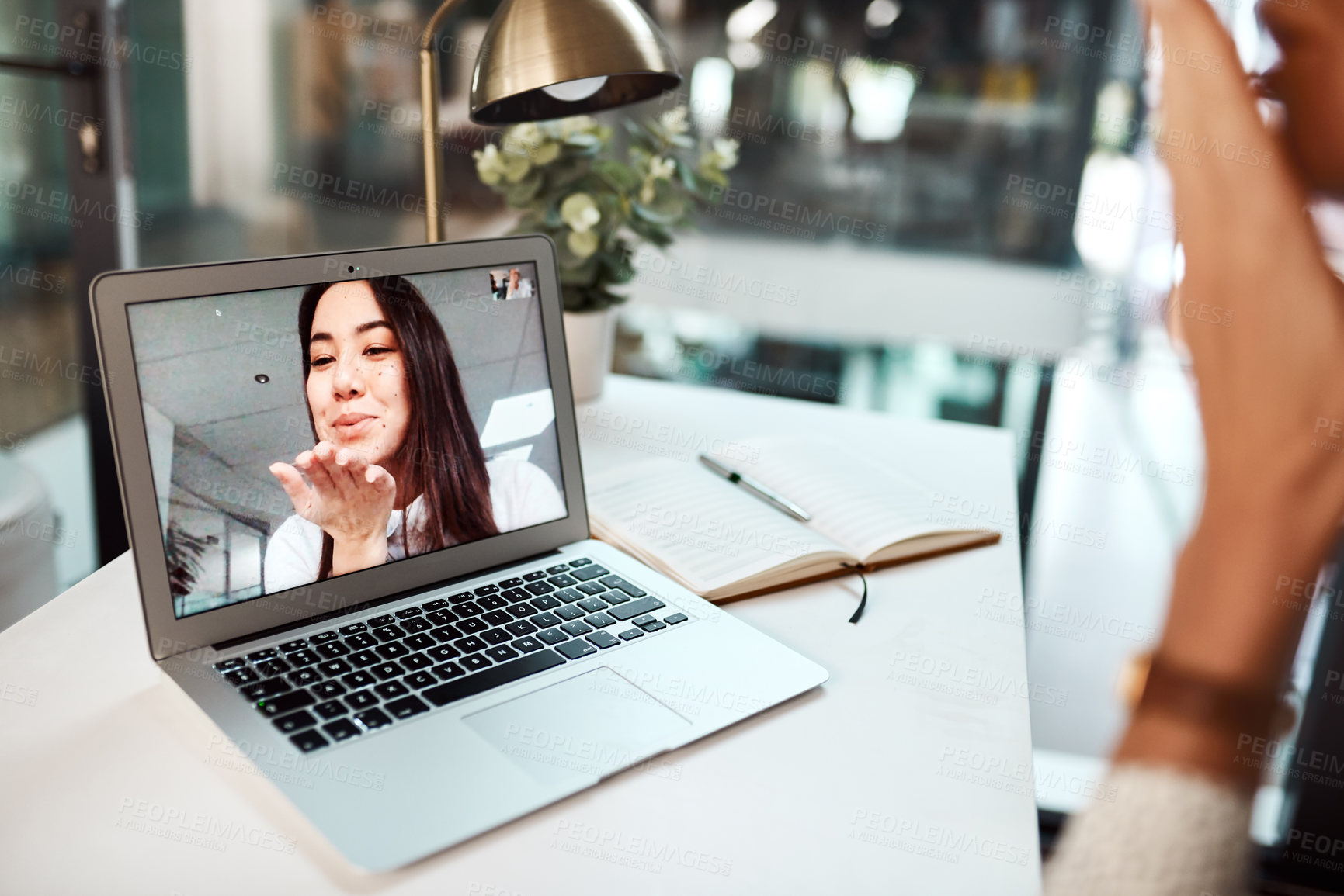 Buy stock photo Shot of a young woman blowing a kiss while appearing on a laptop screen during a video call