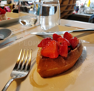 Buy stock photo Shot of strawberries served on a freshly made waffle at a restaurant in Prague