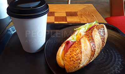 Buy stock photo Shot of a submarine sandwich and coffee on a table at a restaurant