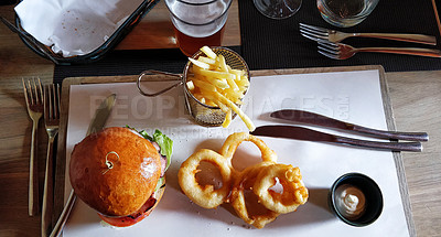 Buy stock photo Shot of a beef burger served with onion rings and potato fries at a restaurant