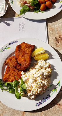 Buy stock photo Shot of chicken schnitzel served with a potato salad at a restaurant in Kutna Hora, Prague