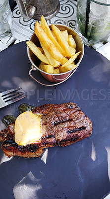 Buy stock photo Shot of a juicy cut of grass fed steak, fries and marrow butter served on a plate in a restaurant