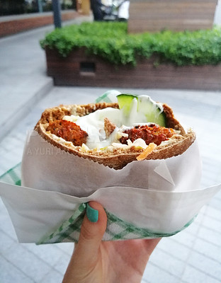 Buy stock photo Cropped shot of a woman holding a freshly made falafel pita wrap