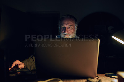 Buy stock photo Shot of a senior man using a laptop during the night at home