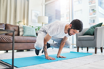 Buy stock photo Shot of a handsome young man practising yoga in his living room at home