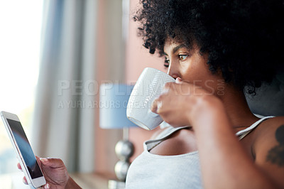 Buy stock photo Cropped shot of a woman using her cellphone while having coffee in bed
