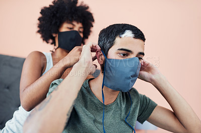 Buy stock photo Cropped shot of a woman helping her boyfriend with his mask