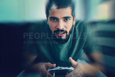 Buy stock photo Cropped shot of a young man sitting on the couch while playing video games
