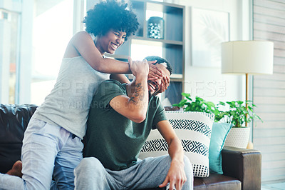 Buy stock photo Shot of a woman covering her boyfriend's eyes while sitting on a couch